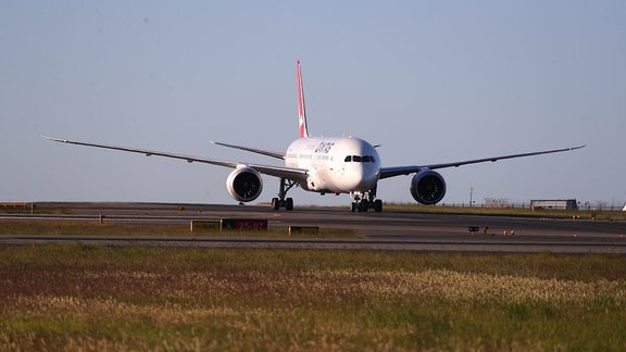 Langstreckenflugzeug von Qantas auf dem Rollfeld, Blick auf das Flugzeug von vorn, im Vordergrund rotbraunes Gras