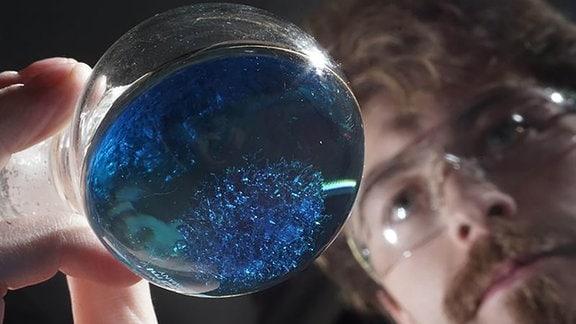 Der Jenaer Doktorand Benjamin Kintzel betrachtet ein Laborgefäß mit Kristallen eines neuartigen Moleküls, das möglicherweise in einem Quantencomputer Verwendung finden kann