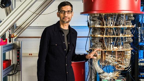 Mann mit kurzen Haaren, Brille und Bart sowie scharzem aufgeknöpftem Oberteil in einem Labor mit vielen Kabel und Computertechnik