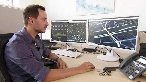 Mann schaut auf Monitore auf einem Schreibtisch