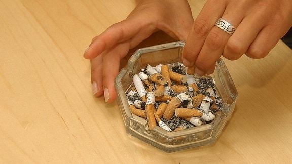 Junge Raucherin drückt ihre Zigarette in einem vollen Aschenbecher aus.
