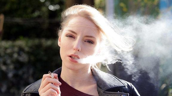 portrait einer jungen blonden frau mit zigarette