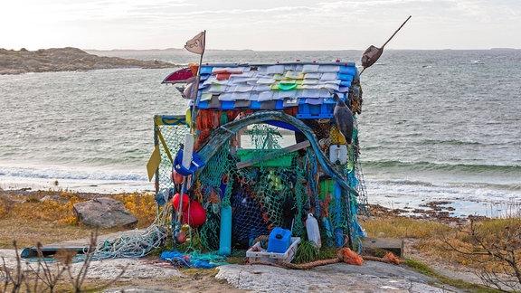 Eine kleine Hütte, die aus verschiedenen bunten Plastikmüllteilen (z.B. Flaschen und ein Netz) zusammengebaut wurde, an einem Strand. Im Hintergrund Wasser bis zum Horizont.
