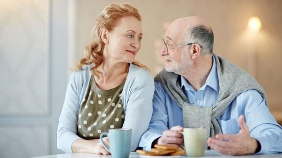 Ehepaar schaut sich beim Kaffee in die Augen.