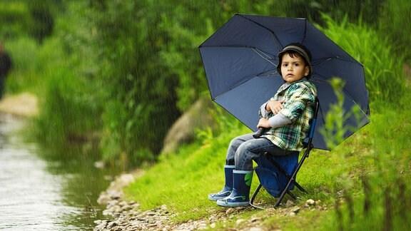 Kleiner Junge  mit Regenschirm sitzt auf einem Klappstuhl