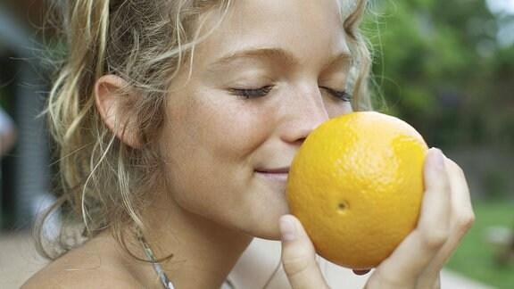 Eine junge Frau riecht an einer Zitrone