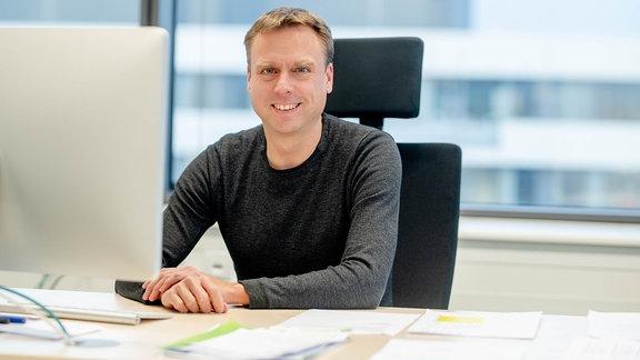 Ein lächelnder Mann an einem Schreibtisch