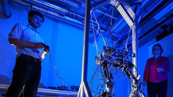 Ein Roboter-Gelenk im Testeinsatz. Ein Forscher (lnks) steuert, eine Forscherin (rechts) schaut zu