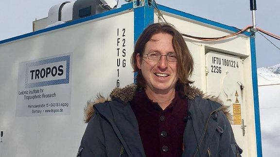 Ein Mann mit Winterjacke vor einem Forschungscontainer mit der Aufschrift TROPOS