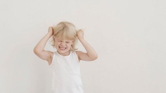 Wütender Junge zieht sich am eigenen Haar