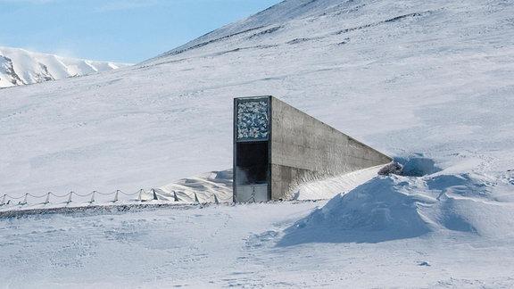 Teilansicht eines leicht mit Schnee bedeckten Berges, in den ein Portal aus Beton eingelassen ist.