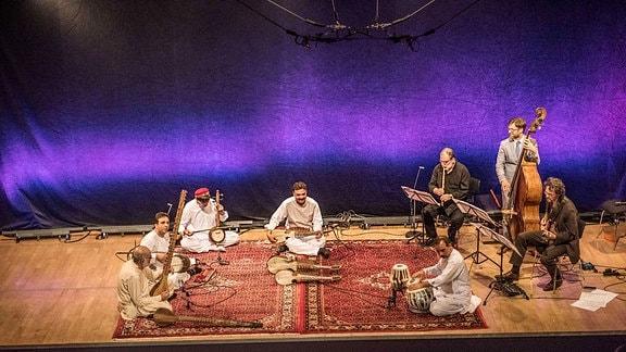 Blick auf eine Bühne fünf Musiker sitzen mit orientalischen Musikinstrumenten auf einem teppich, rechts daneben - ein Flötist, ein Gitarrist und ein Kontrabassist.