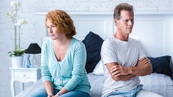 Eine Frau und ein Mann sitzen getrennt auf einem Bett.