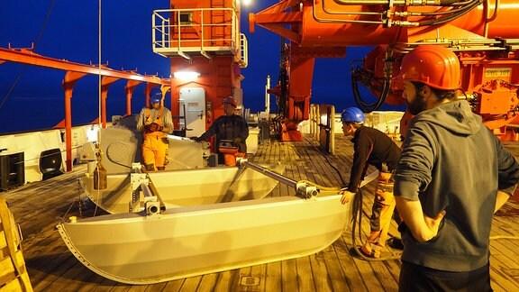 Menschen hantieren an Bord eines Schiffes mit Geräten
