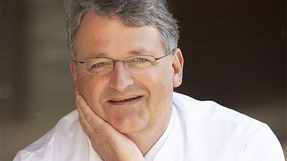 Porträt von Prof. Dr. Thomas Schläpfer. Er hat graue Haare und trägt eine schmale Brille. Sein Gesicht ist in eine Hand gestützt.