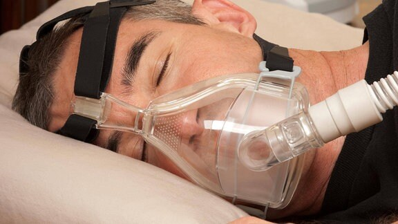Mann schläft mit Atemmaske