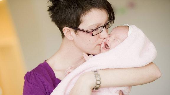 Mutter küsst ihr schreiendes Baby.