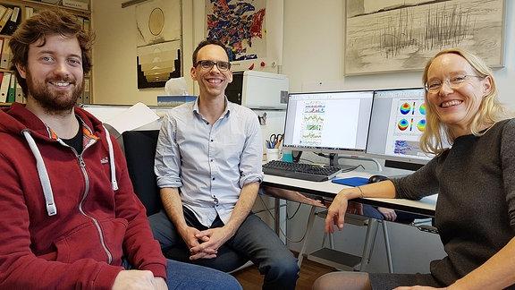 Zwei Männer und eine Frau sitzen an einem Computertisch und lächeln in die Kamera.