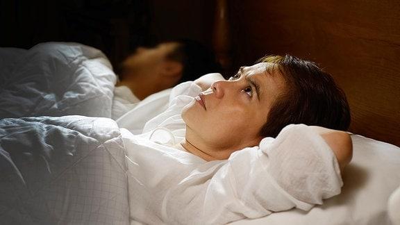 Eine Person liegt wach im Bett.