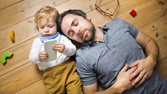 Ein Mann schläft neben einem Kleinkind