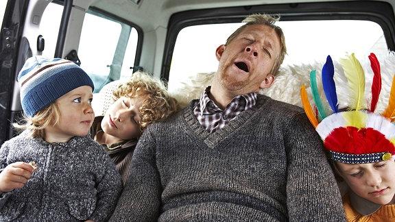 Ein Mann gähnt zwischen drei Kleinkindern auf dem Rücksitz eines Autos