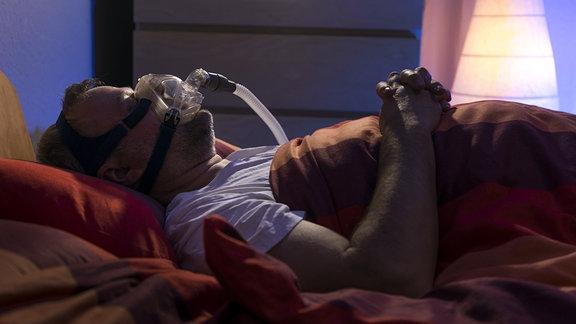 Mann mit Schlafapnoe-Syndrom, trägt beim Schlafen eine CPAP Maske (Atem-Schlafmaske)