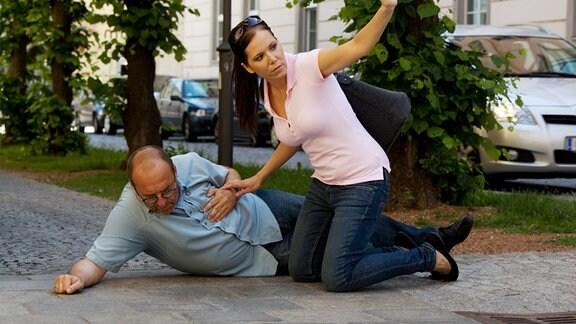 Ein Mann liegt mit Schmerzen auf der Straße und eine Frau hilft ihm