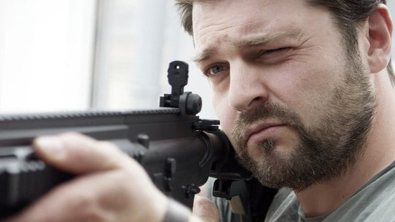 Der Autor, Schauspieler und Blogger Schlecky Silberstein (bürgerlich Christian Brandes) mit einem Schnellfeuergewehr im Anschlag.