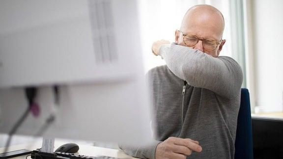 Ein Mann im Büro niest in seine Armbeuge.