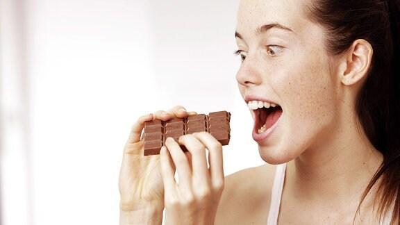 Frau beiߟt herzhaft in eine Tafel Schokolade