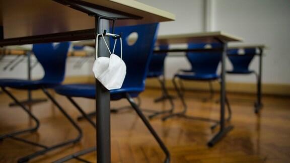Mundschutzmaske hängt an einer Schulbank