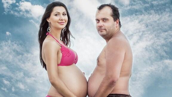 Schwangere Frau und Mann mit dickem Bauch in der selben Pose ihren Bauch umfassend.
