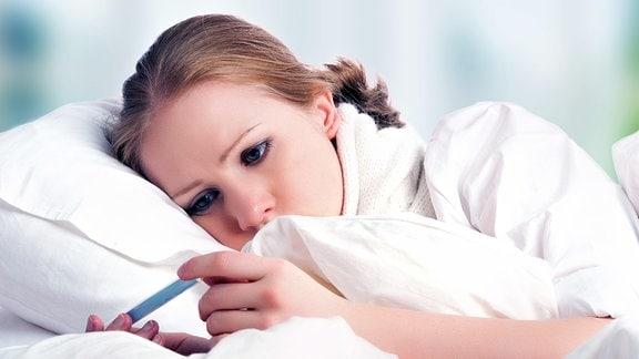 Frau mit Fieberthermometer im Bett