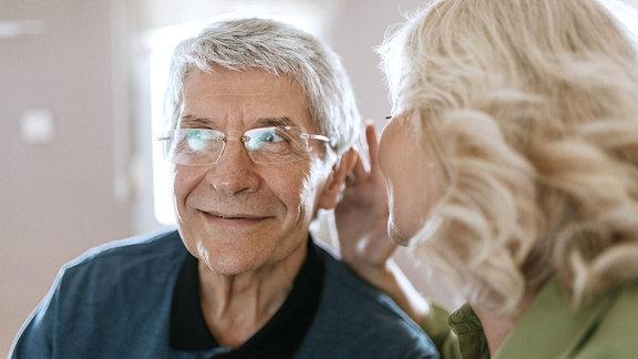 Eine Frau flüstert einem Mann etwas ins Ohr
