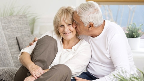 Ein älteres Pärchen sitzt auf dem Sofa und er küsst sie.