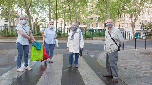 Gruppe von Senioren auf Spaziergang in Paris mit Mundschutz.