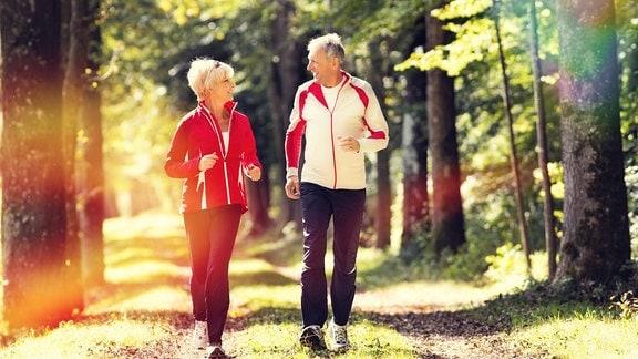 Seniorin und Senior joggen im Wald.