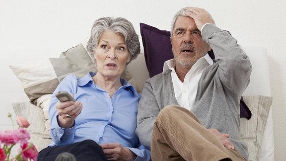 Senioren sitzen auf der Couch und schauen Fernsehen.
