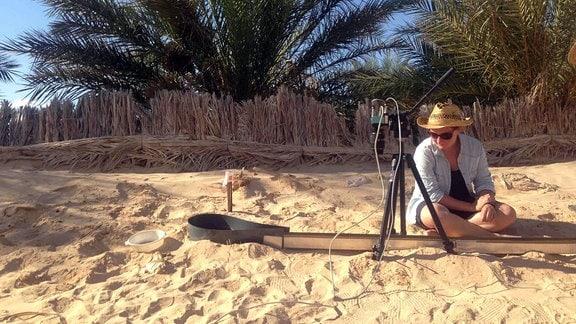 Eine Frau sitzt vor einer silbernen Leitung im Sand
