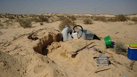 Ein Mann gräbt in einer Wüste einen Graben.