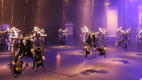 Von der Decke hängen Roboteranzüge, die in lila Licht getaucht sind
