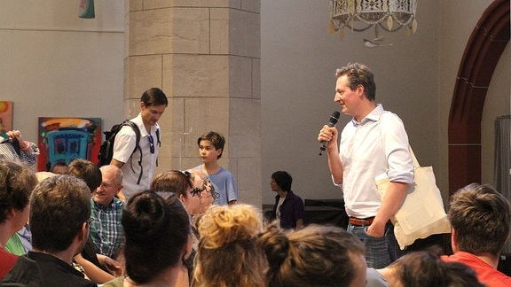 Eckart von Hirschhausen steht mit Mikrofon vor dem Publikum in der Ulrichskirche