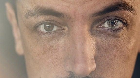 Frontale Nahaufnahme eines dunkelhaariger Mannes mit hochgezogener Augenbraue und Kontaktlinse, die wie eine digitale Kontaktlinse aussieht. Mystischer Lichteinfach und Unschärfe von links.
