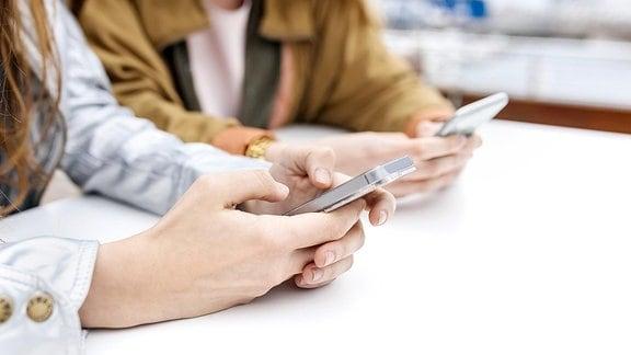 Zwei Frauen, die Nachrichten mit ihrem Smartphone senden.