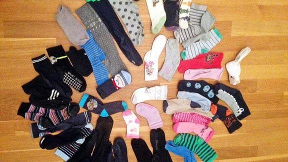 Viele verschiedene Socken liegen am Boden.