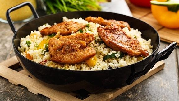 Sojaschnitzel auf Couscous und Gemüse in einer Pfanne