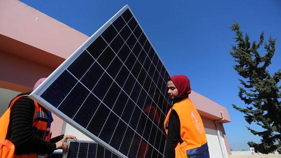 Solarmodule werden von jungen Frauen auf einem Schuldach in Palästina installiert.