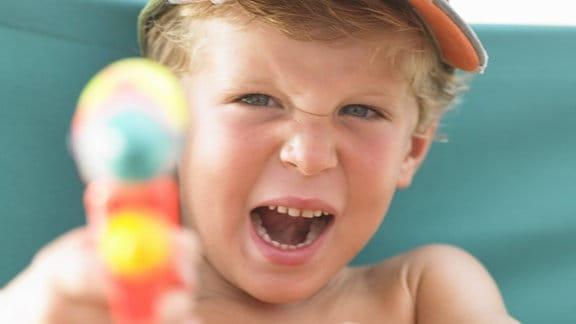 Ein Junge mit einer Wasserpistole
