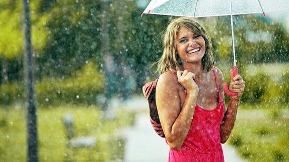 Eine junge Frau mit Schirm in einem Sommerregen