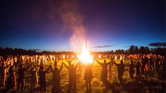 Während einer Sommersonnenwende im Dorf Okunevo versammeln sich die Menschen um ein Lagerfeuer.